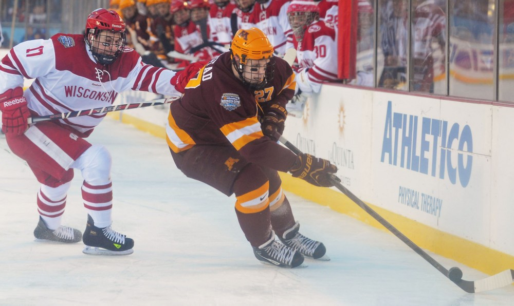 Minnesota forward Nick Bjugstad (27) keeps the puck from Wisconsin forward Nic Kerdiles on Sunday, Feb. 17, 2013, at Soldier Field in Chicago. The Badgers beat the Gophers 3-2.