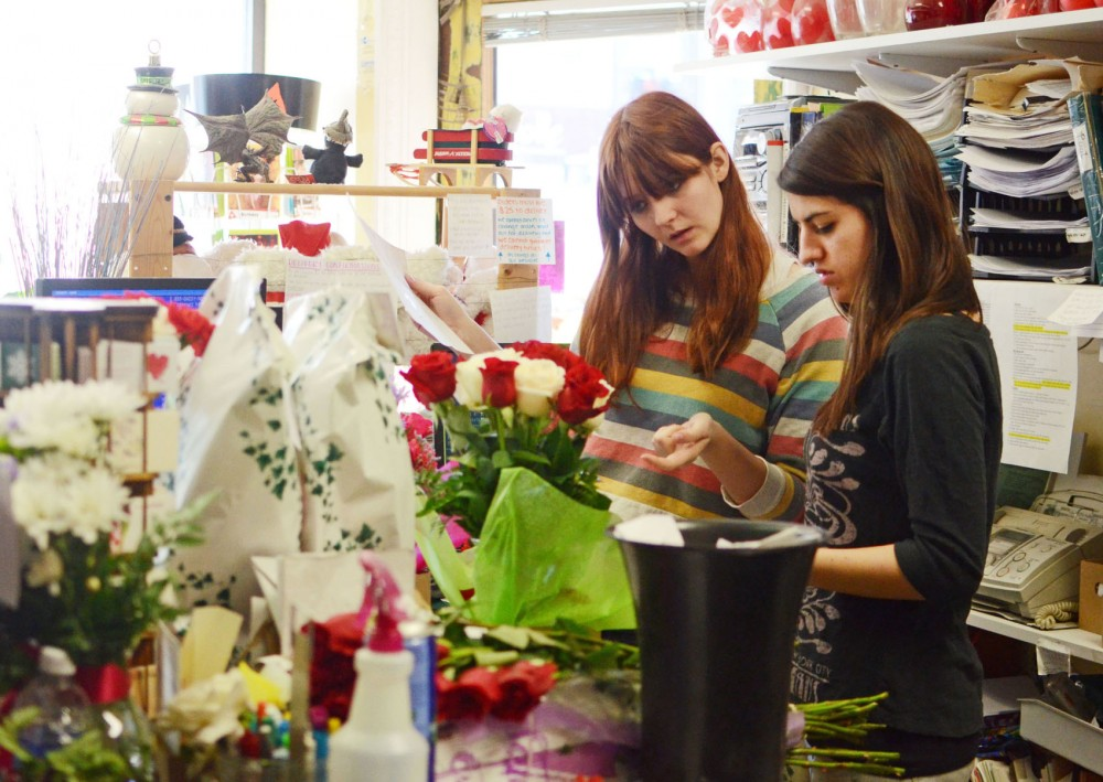 Carly Hall and Tina Zedginidze work on wrapping a floral arrangement Tuesday, Feb. 12, 2013, at Sheffield's Floral in Stadium Village.