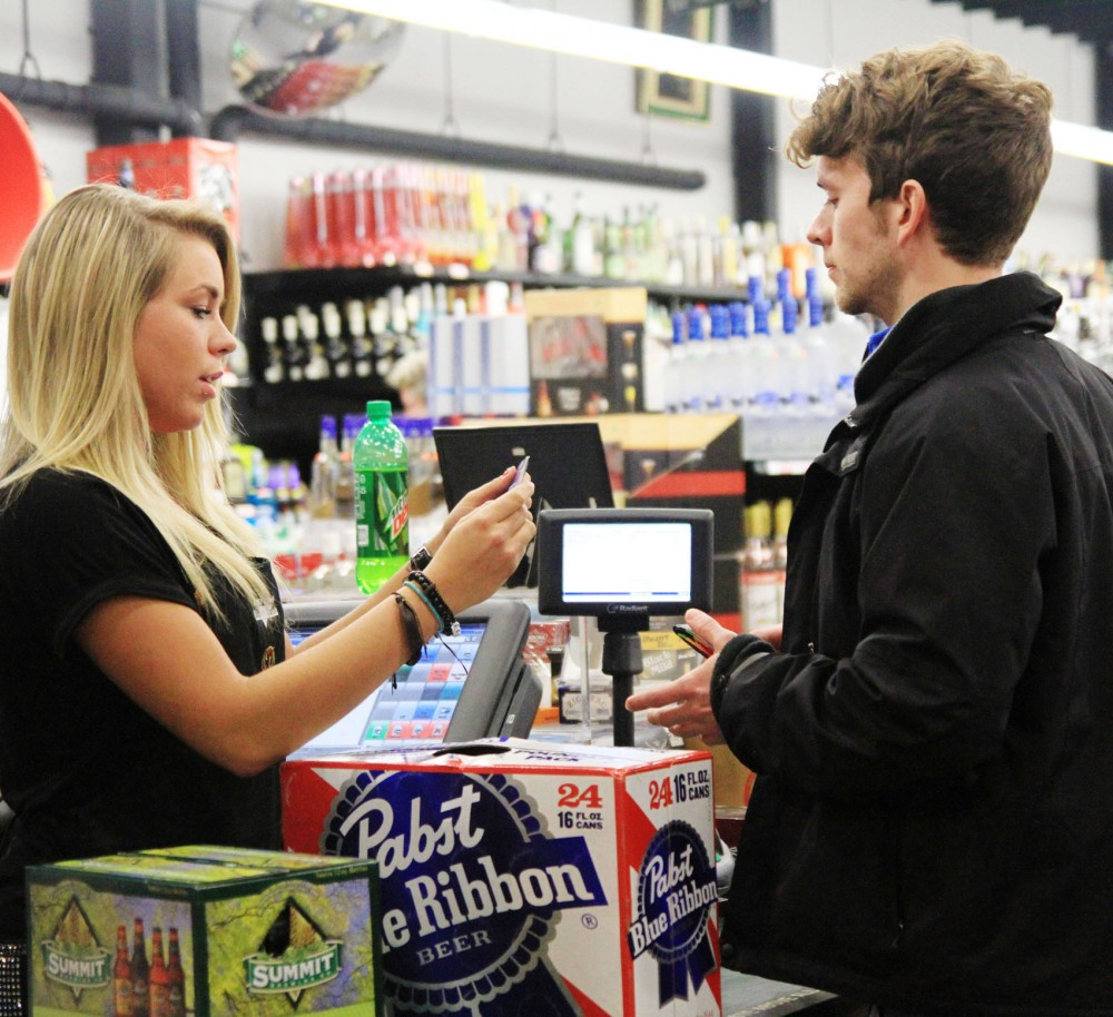 Linguistics second-year Alyssa Rose checks the ID of psychology senior Kevin Tully just before close Saturday, March 2, 2013, at Dinkytown Wine and Spirits. A new ordinance allows the Minneapolis City Council to place mandatory conditions on an uncooperative business.