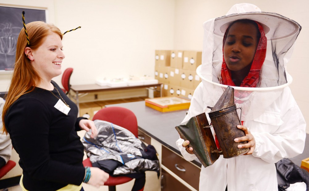 High school student Deqa Mahamoud, right, from Youth Farm in South Minneapolis tries on a beekeeping suit on Friday, March 29, 2013, at Hodson Hall. About 100 high school students visited the St. Paul campus from a variety of different urban farming programs throughout the Twin Cities area.