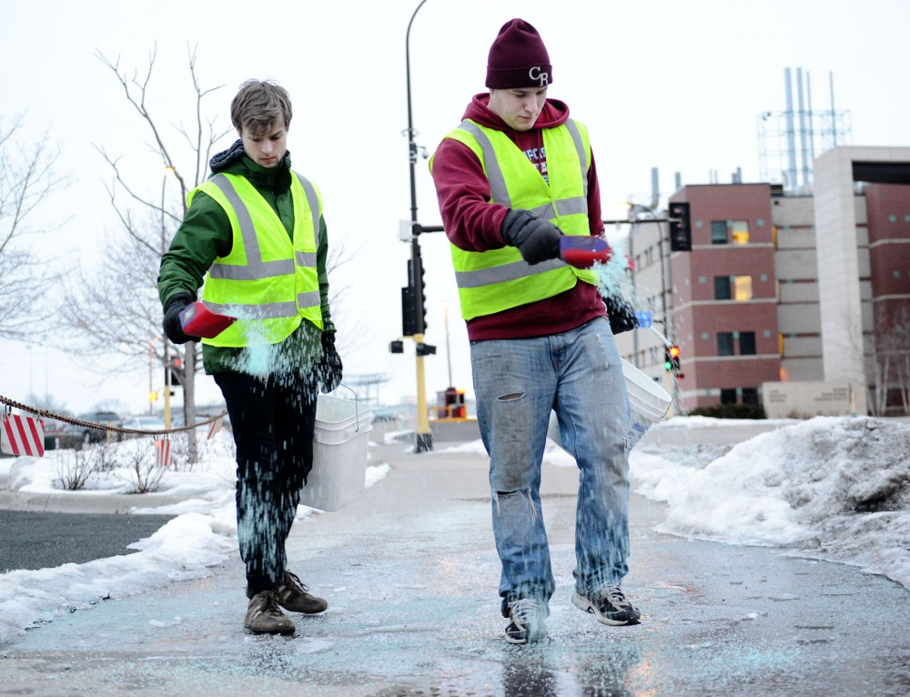 University sophomore Christian Boomgaarden and senior Troy Marschall spread ice melt Monday, March 11, 2013, on the University's East Bank.