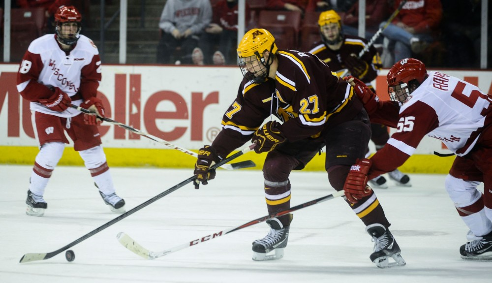 Minnesota forward Nick Bjugstad keeps the puck from Wisconsin forward Joel Ramage on Friday, Feb. 15, 2013, at the Kohl Center in Madison.