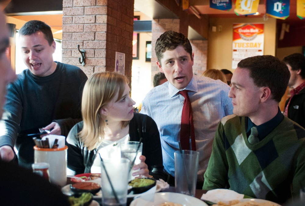 Minneapolis lawyer and Ward 3 City Council candidate Jacob Frey, center, talks to marketing and international business senior Ghee Kaefring, left, and global studies junior Marissa Kramer at a pre-caucus party for Frey Saturday, Feb. 16, 2013, at Burrito Loco in Dinkytown. After Tuesday's caucuses around Minneapolis, the Democratic Labor Party will endorse candidates for city council.