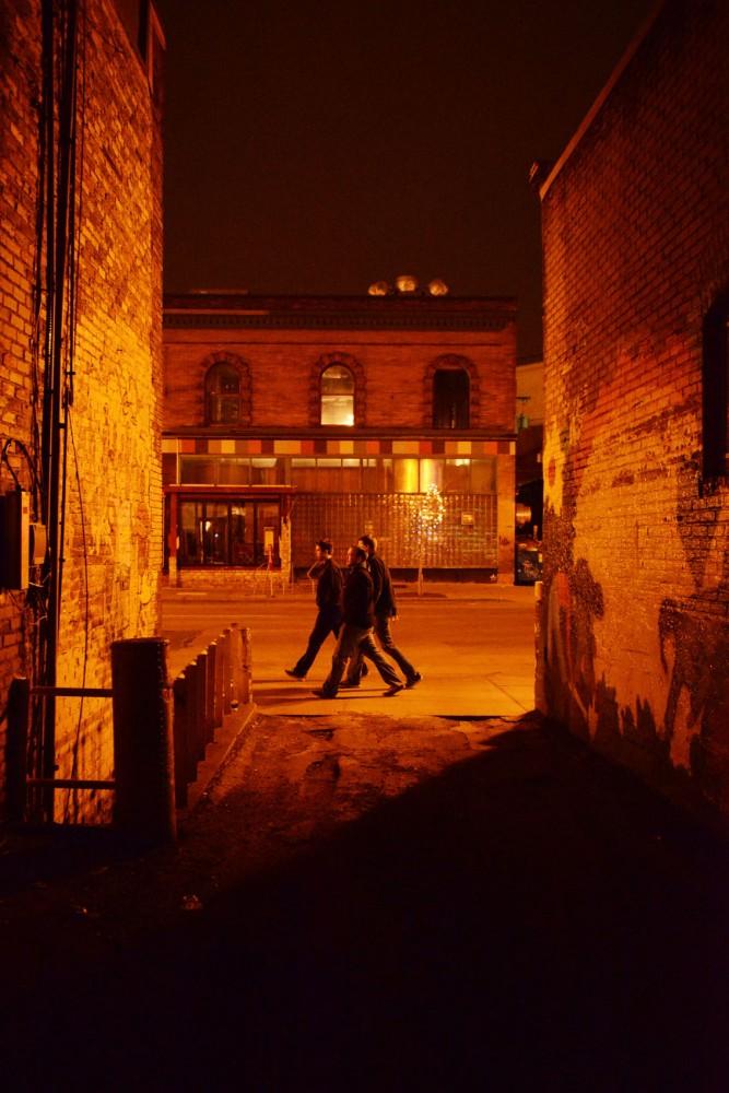 Three men wander down the Fourth Street in Dinkytown.