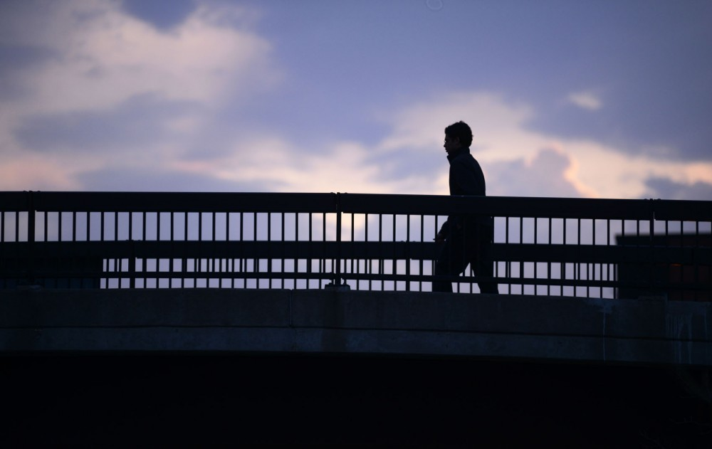 A student walks across the pedestrian bridge over South 4th Street from Middlebrook Hall.