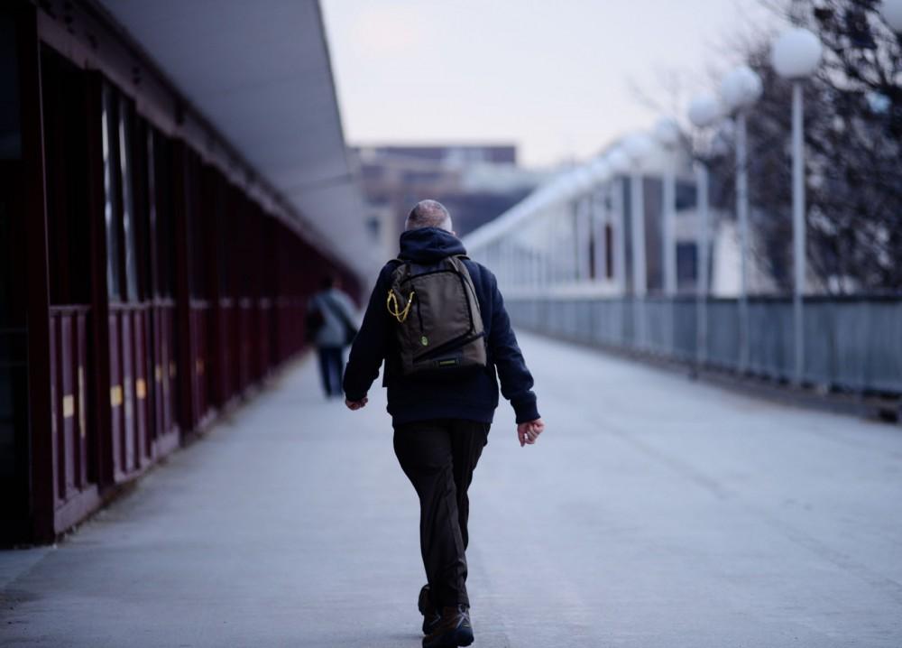A man walks across Washington Avenue Bridge.