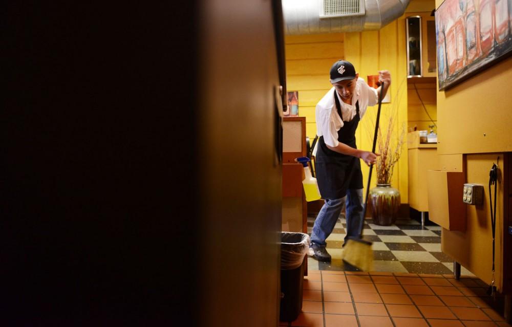 Jose Alfredo Navas Quevedo sweeps the floor at Kafé 412 before opening in Dinkytown.