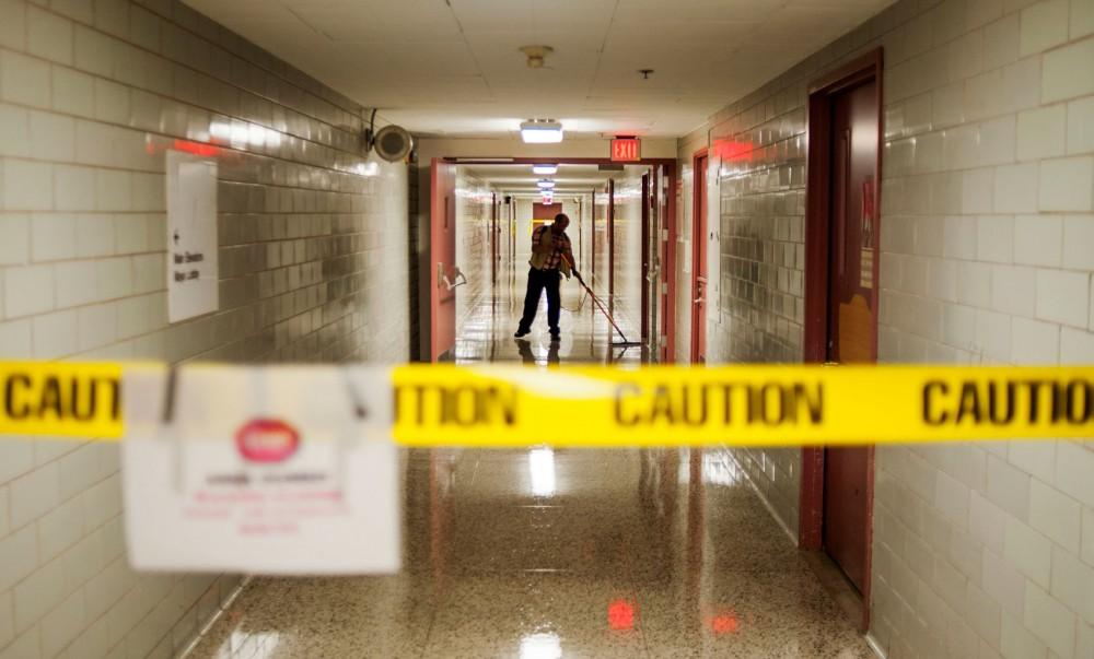 A custodian waxes a hallway beneath the Mayo Building.