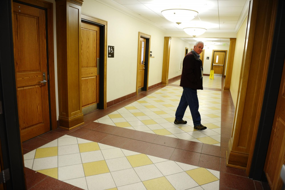 A university facility management worker guards the door of a first floor men's bathroom of Nicholson Hall while a crew cleans the a written threat from a stall wall inside Friday, April 12, 2013.