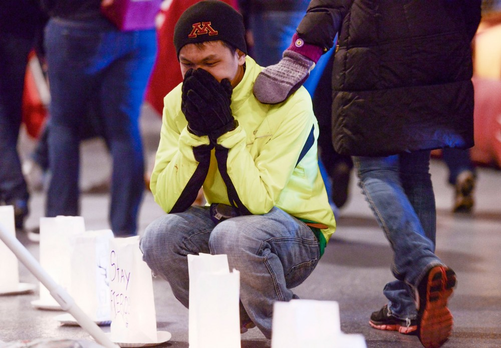 Freshman Francis Chang kneels by a luminaria bag dedicated to his father at the Relay for Life event on Friday, April 5, 2013, at TCF Stadium.