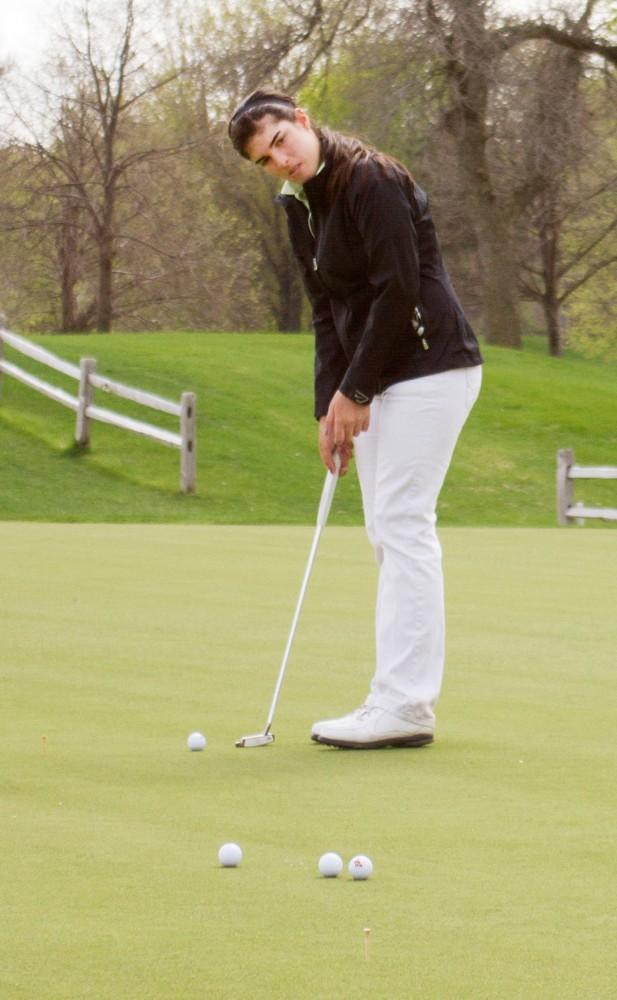 Minnesota golfer Carmen Laguna practices putting Tuesday, April 17, 2012, at the Les Bolstad Golf Course in Falcon Heights, Minn.