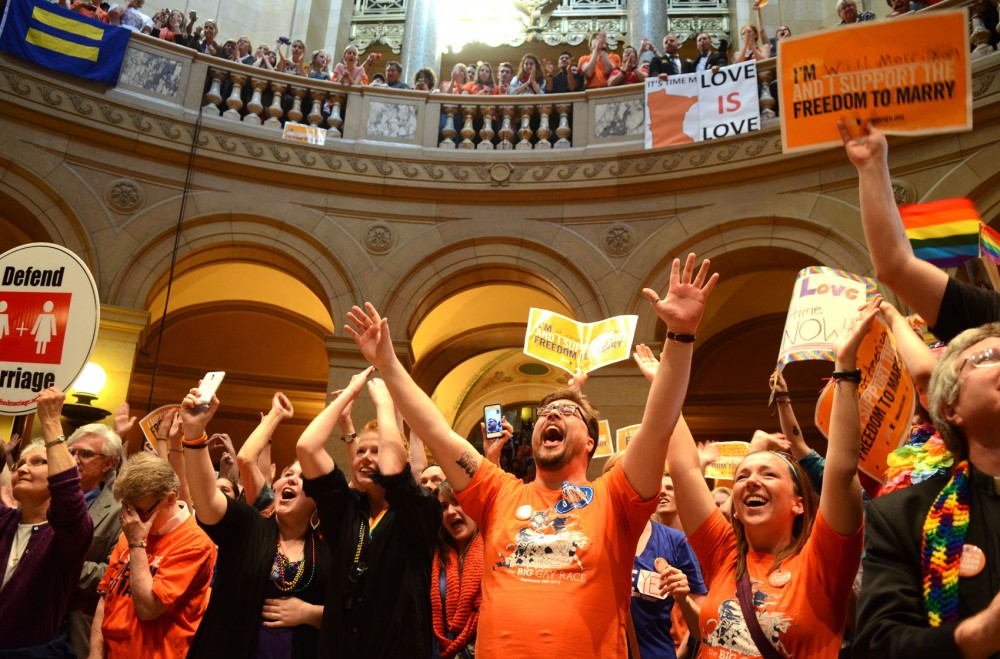 Hundreds gathered in the rotunda of the capital cheer as it is announced that the bill had passed, Monday afternoon.