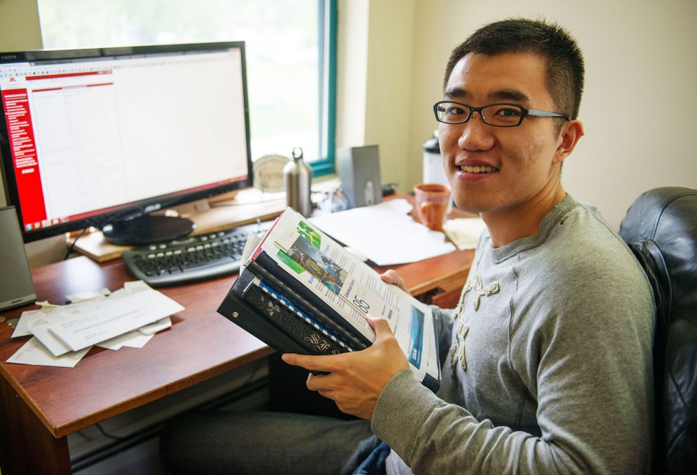 University of Minnesota graduate Michael Sun Haonan holds stacks of forms, guides and applications in his Minneapolis apartment on May 27, 2013. As an international student, the process for staying in the United States to work or attend graduate school is more complicated, such as finding employers willing to sponsor work visas.