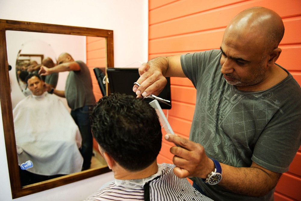 Casablanca hair design owner Abdulhad Batal cuts the hair of Cultural Studies & Comparative Literature Studies lecturer and 10 year customer Imed Labidi. Casablanca, which opened in Dinkytown 15 years ago, would be affected by the Opus development and the delay over Dinkytown environmental concerns.