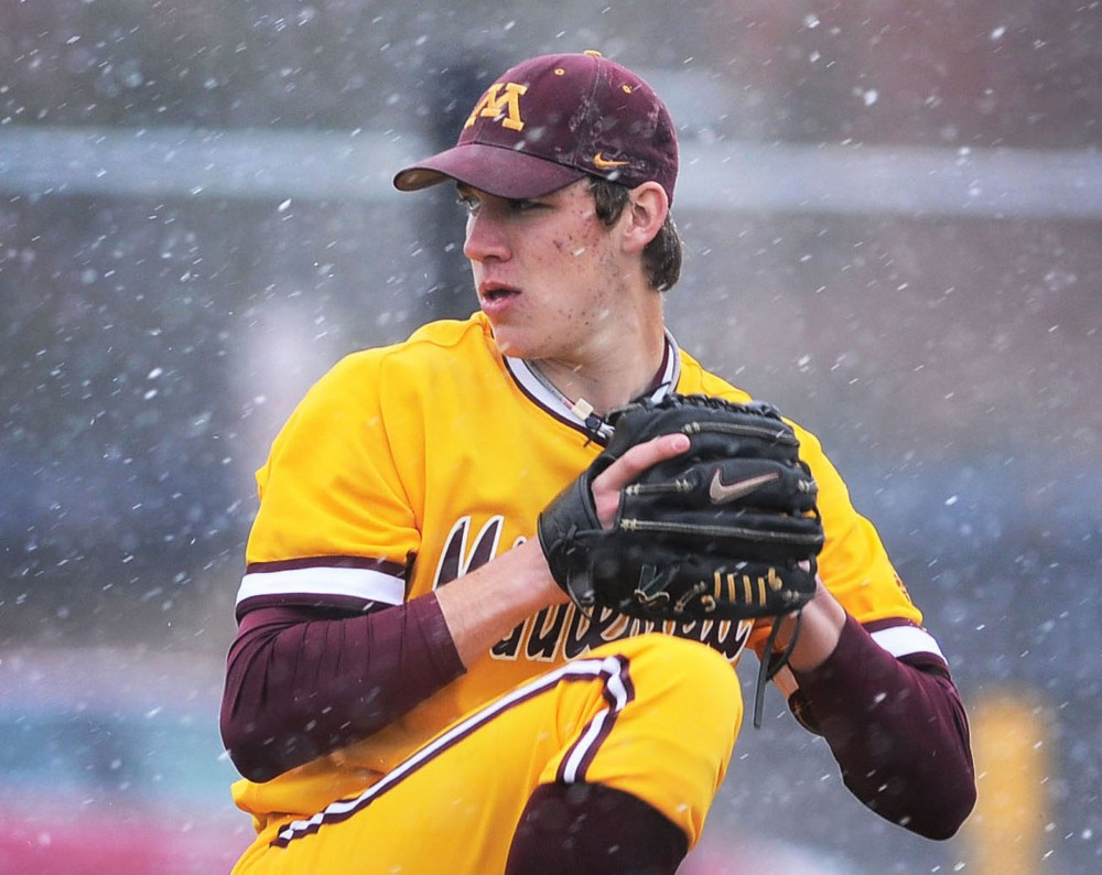 Minnesota junior Tom Windle pitches through sleet and snow during the opening game at Siebert Field on Friday, April 5, 2013.