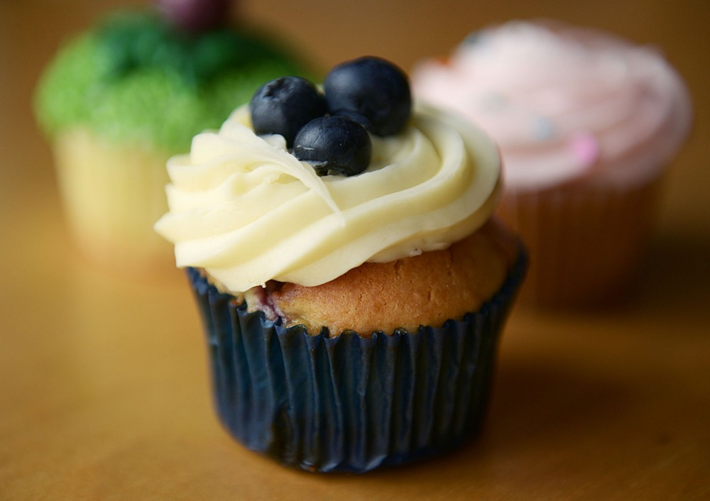 A blueberry cheesecake cupcake topped with smooth cream cheese frosting and blueberries from Cupcake on University Avenue.
