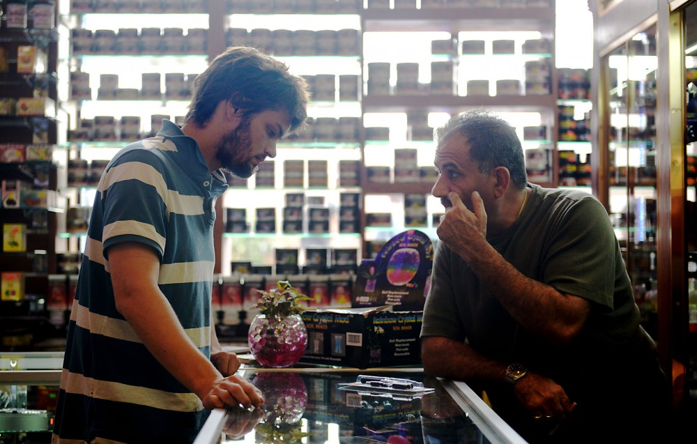 Smokedale store manager David Yousef and customer Johnathan Martiny discuss e-cigarette options on Tuesday, June 18, 2013, at Smokedale in Stadium Village. Yousef believes e-cigarettes are likely to become much more popular after the cigarette tax is implemented.