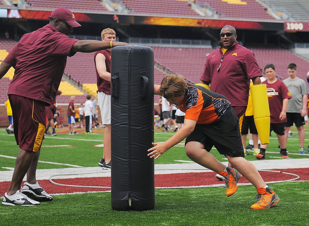 Camper Aj Mazzucchi, 11, tackles a weighted bag during one of a series of football camps for youth which were hosted by Jerry Kill at TCF Stadium on Monday June 17th, 2013.