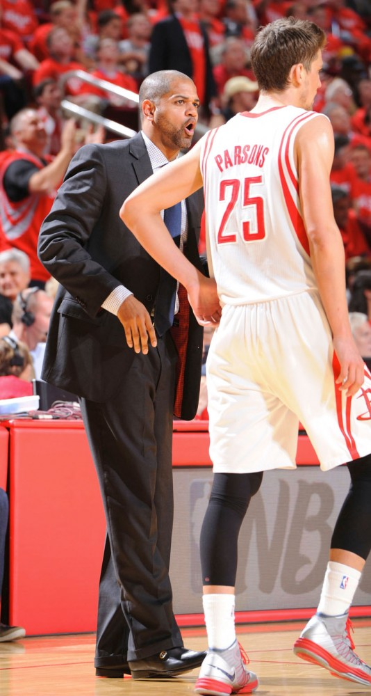 Houston Rockets assistant coach J.B. Bickerstaff coaches forward Chandler Parsons during a game.