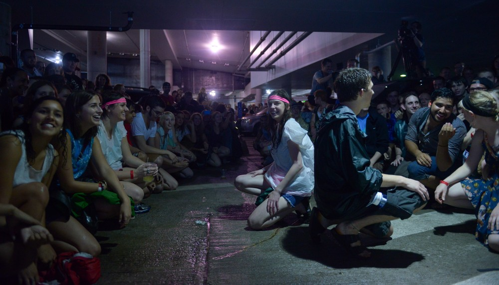 Rock the Garden attendees crouch to the ground before a dance competition during Dan Deacon's set in the parking garage of The Walker Art Center during the Rock the Garden concert on Saturday June 15th, 2013. Deacon is known for getting his audience involved with his extravagant live performances.