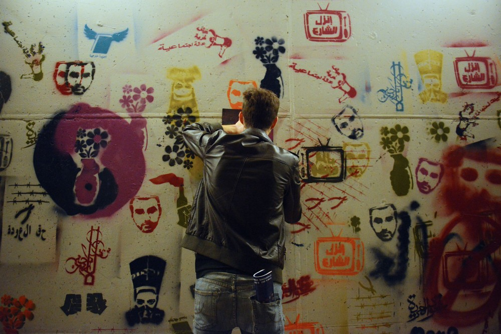 A man spray paints the wall in a participatory work created by Islam Shabana, Hamza Salim, Hend Kheera and Dunya Alwan titled Underpass of the Eyes of Freedom during Northern Spark in St. Paul.