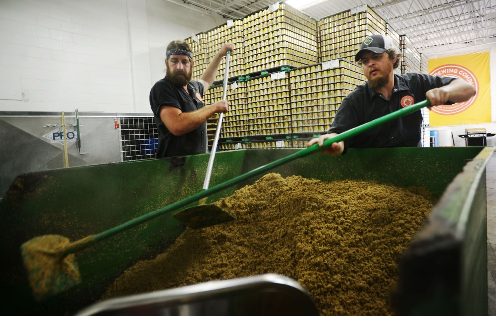 Head brewer Josh Bischoff, right, and assistant brewer Chad Hilgenberg shovel out residual grain after the lautering process, separating liquid wort from the grains, is complete at Indeed Brewery Company on Tuesday, July 2, 2013.