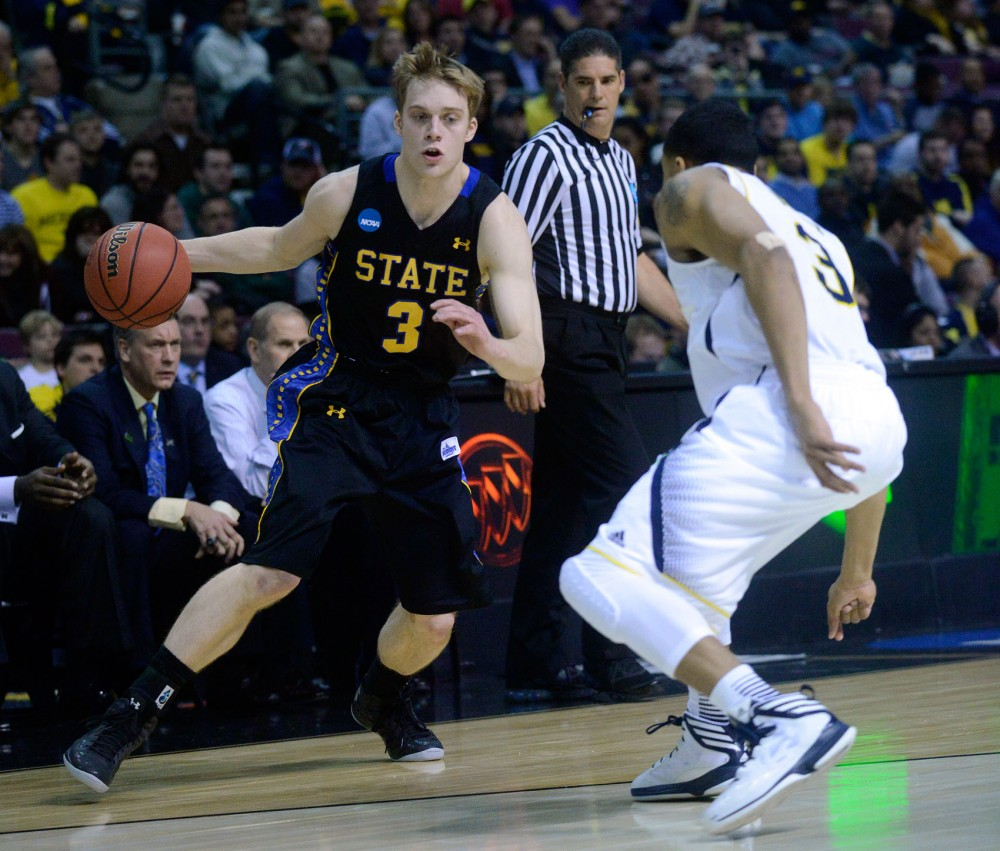SDSU's Nate Wolters dribbles past Michigan's Trey Burke in the second round game of the NCAA Division 1 men's basketball tournament in Auburn Hills, Mich, March 21, 2013.