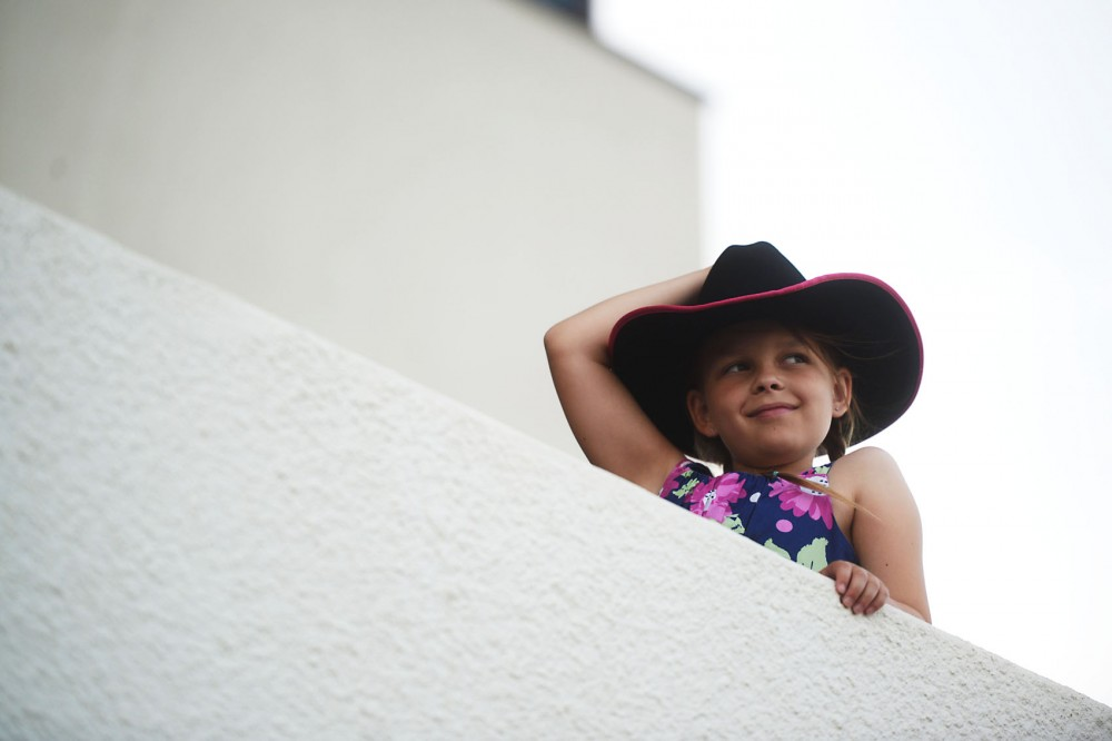 9-year-old Aria Jamison leans over the edge as she watches the beginning of a horse race at Canterbury Park on Friday, July 12, 2013.