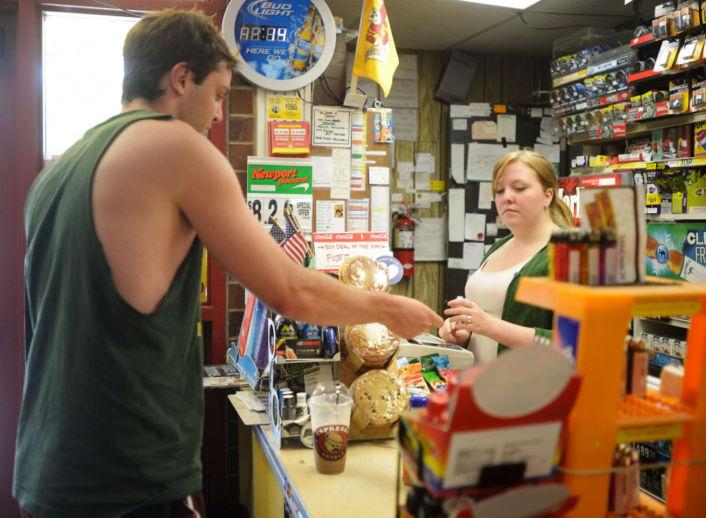 Economics junior Grant Savage pays Staci Caldow, right, for items at House of Hanson July 20, 2013, in Dinkytown. Smaller grocery stores, such as House of Hanson, are being affected by bigger chain convenience stores such as CVS Pharmacy and Walgreens.