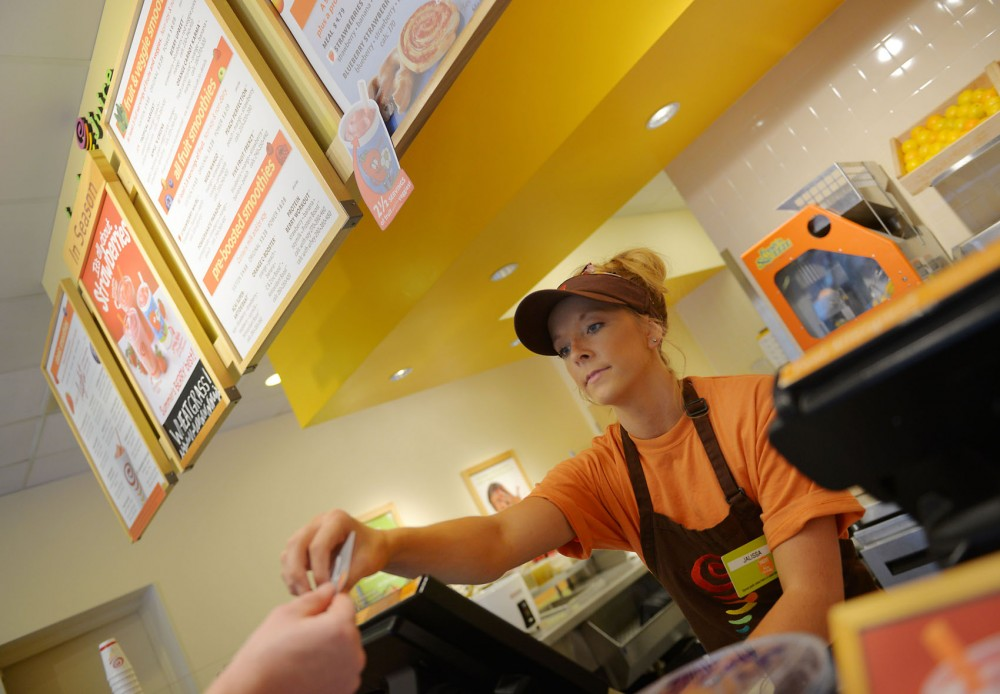 Jamba Juice employee Jalissa Engelage takes a customer's credit card to pay for his drink on Monday, July 29, 2013, in Stadium Village. Jamba Juice is one of the few --