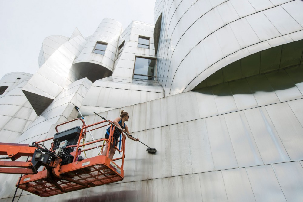 Weisman event coordinator Emily Foxen and director of security and building operations John Allen clean the stainless steal exterior of the museum on Thursday, July 25, 2013. The museum undergoes cleaning by the staff at the Weisman every two years or so.