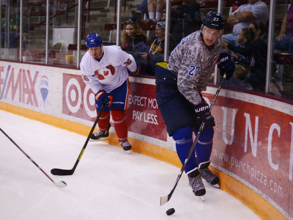 Former Gophers forward Nick Bjugstad and New York Islanders left wing Eric Boulton play during the Defending the Blue Line charity game on Saturday, Aug. 3, 2013, at Ridder Arena.