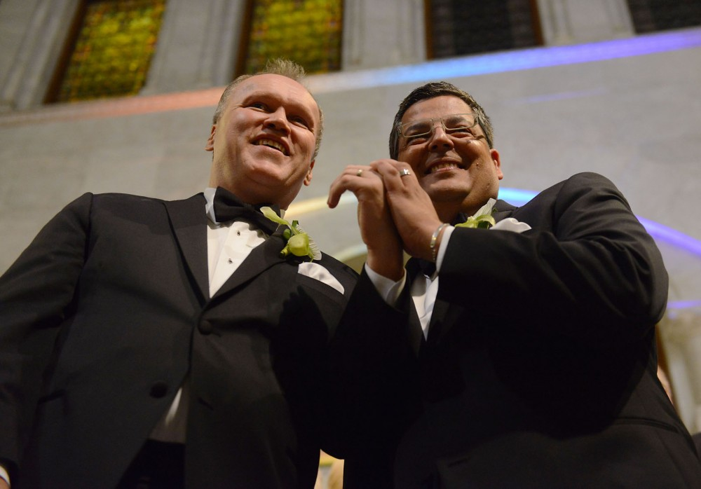 Jeff Isaacson, left, and his new husband Al Giraud, right, of Minneapolis, display their rings after Mayor R.T. Rybak pronounces them legally married August 1, 2013, at Minneapolis City Hall. Isaacson and Giraud became the second legally married same-sex couple in Minnesota.