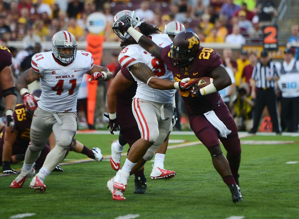 Minnesota running back Donnell Kirkwood stiff arms UNLV player during Thursday's season opener at TCF Stadium. Gophers went on to win 51-23 against UNLV.