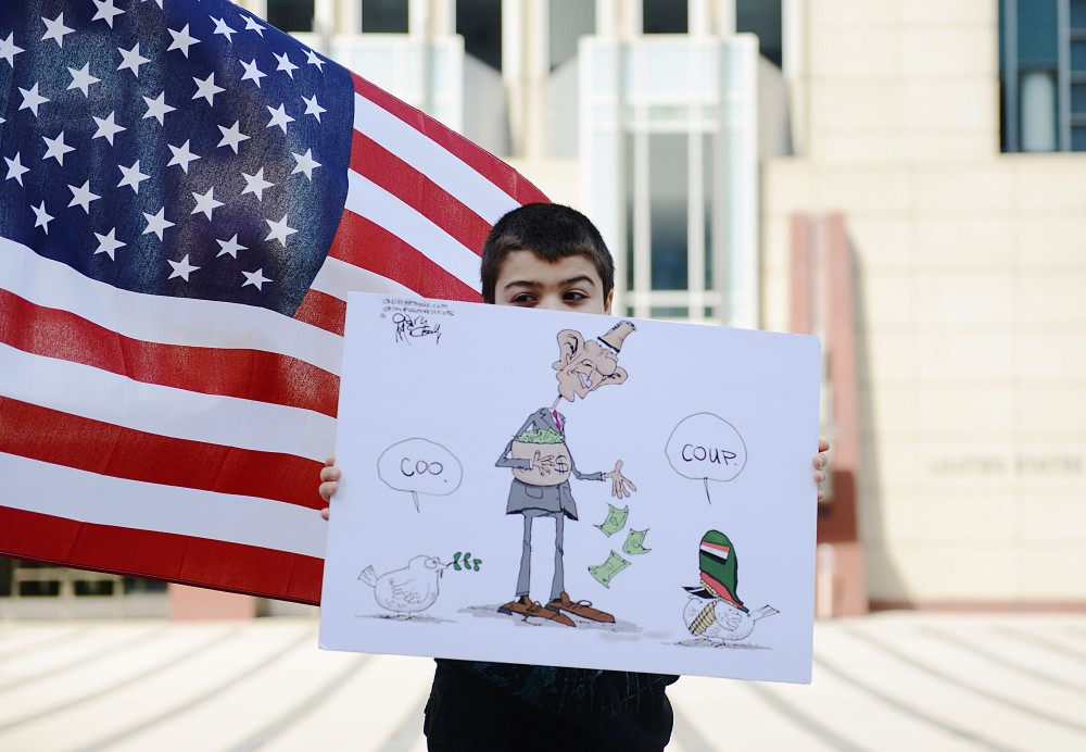 Suhaib Elkholy holds a political cartoon on a poster in protest, Friday afternoon downtown Minneapolis.