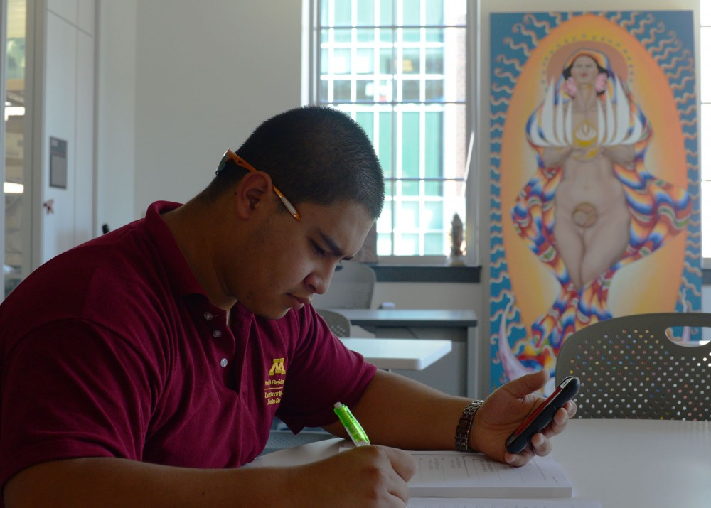 Junior Miguel Jimenez studies at the La Raza Student Cultural Center's office in Coffman Union on Friday afternoon in front of the only mural left from the student group's previous office space. Student groups with offices on the second floor of Coffman were not able to preserve the murals after the building's second-floor renovation and were restricted in how they personalize their spaces.