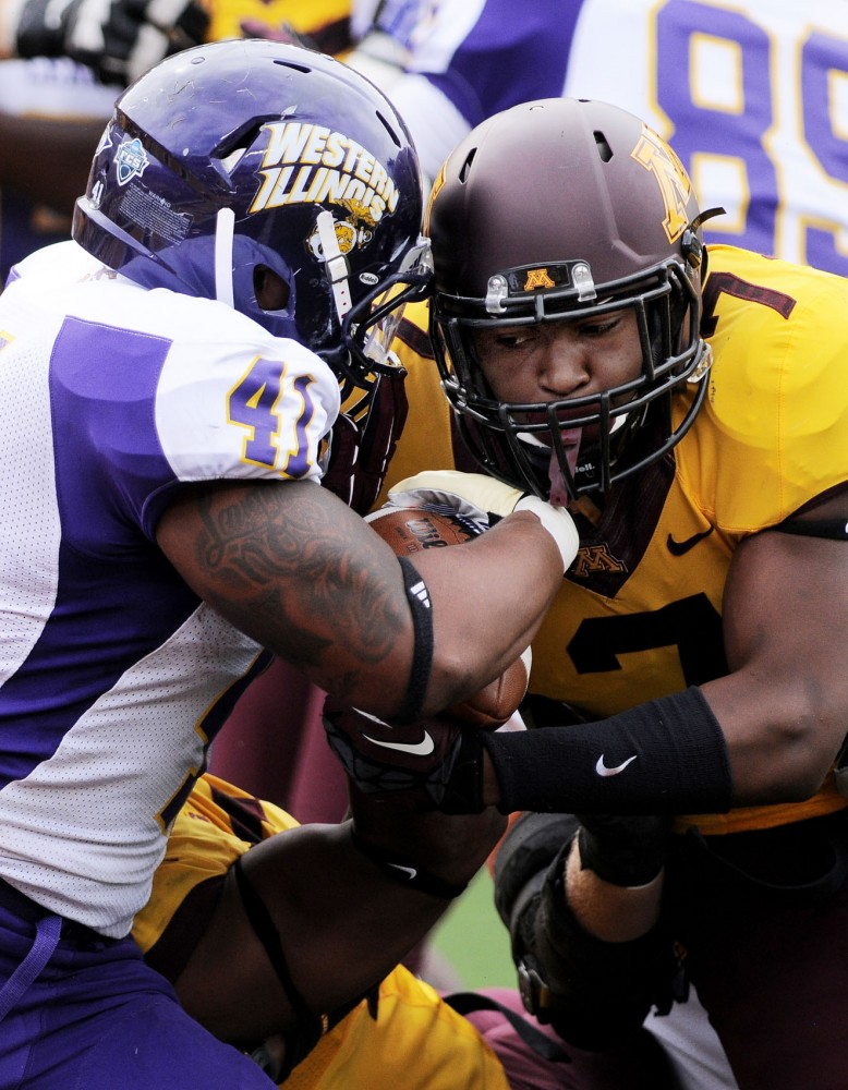 Minnesota defensive back Damarius Travis fights for the football against Western Illinois running back Nikko Watson on Saturday at TCF Bank Stadium.