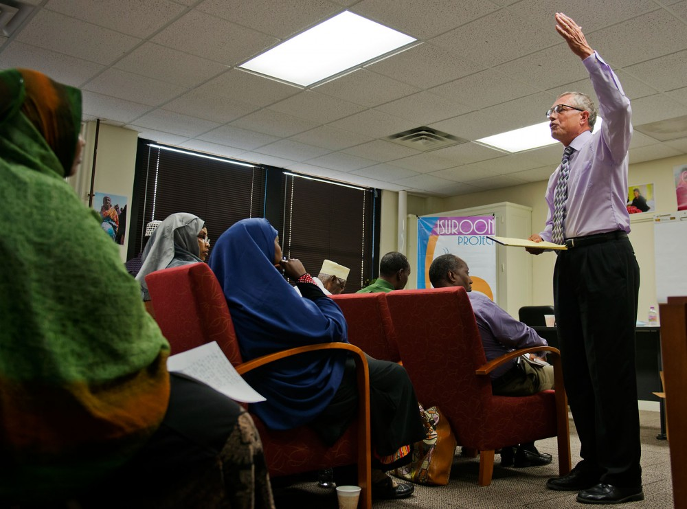"Humphrey School fellow and former Speaker of the Minnesota House Steve Sviguum explains the process of passing a bill in a workshop entitled  ""Governing 101"" on September 6, 2013 in Sabathani Community Center. Sviguum partnered with Isuroon, a Minneapolis-based organization dedicated to Somali women's health issues, to give a series of workshops to teach Somali men and women about the Legislative process."