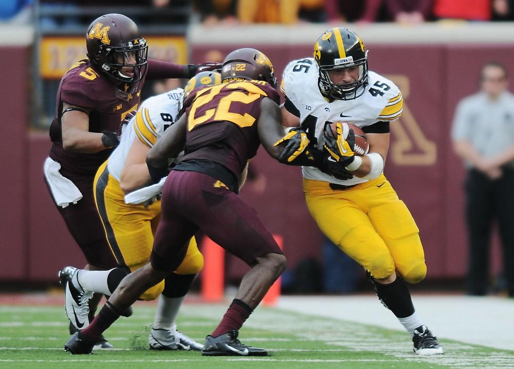 Iowa running back Mark Weisman blocks Minnesota defensive back Jeremy Baltazar on Saturday afternoon at TCF Bank Stadium.