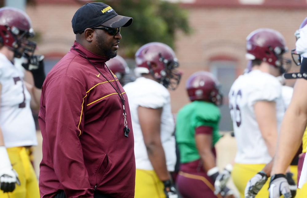 Gophers football running backs coach Brian Anderson watches as the football players warm up for practice on Tuesday, Sept. 10, 2013, at the Bierman Field.