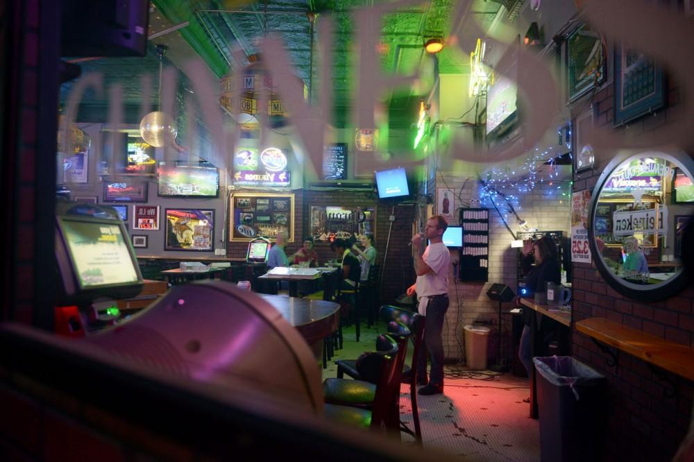 Bartender Ryan Fuchs sings Monday evening at Otter Saloon.