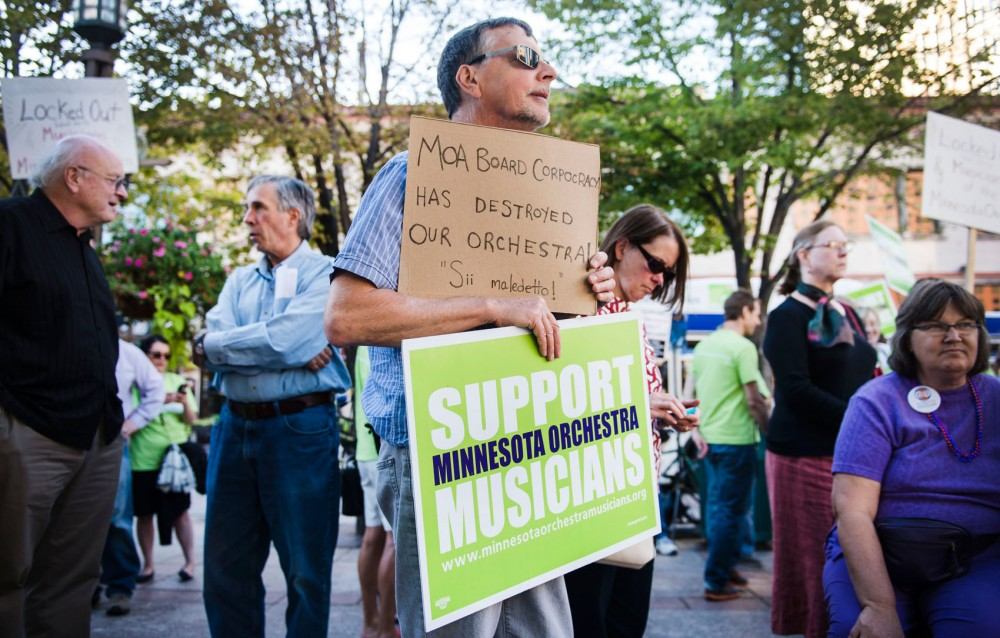 Kurt Rusterholz holds signs in support of Minnesota Orchestra musicians and against the lockout on Tuesday evening outside Orchestra Hall downtown Minneapolis.