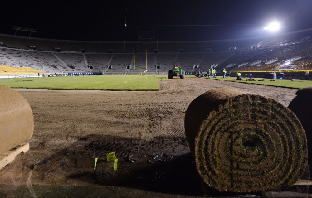 A grounds crew lays fresh grass at the University of Notre Dame's Stadium on Friday, Oct. 4, 2013.