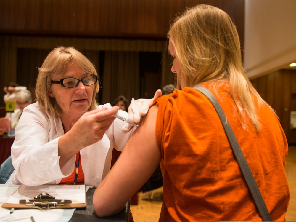 Registered nurse Lorelee Miner gives freshman animal science major Andrea Engstrom a flu shot, Thursday afternoon at the St. Paul Student Center.