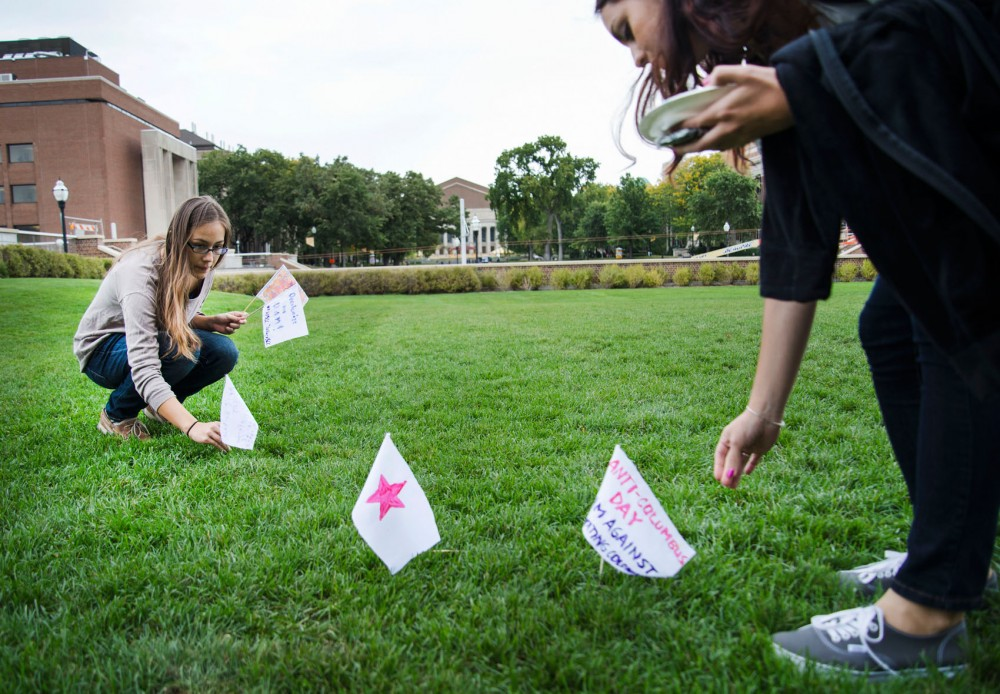 Seniors Stephanie Zadora and Laura Serrano place flags in the ground for La Raza Student Cultural Center and the American Indian Student Cultural Center's Anti-Columbus Day, Monday at Coffman Union.