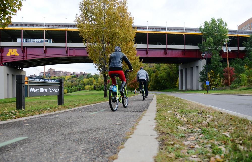 Pedestrians bike on the West River trails located under Washington Avenue bridge on Saturday, Oct. 19, 2013.