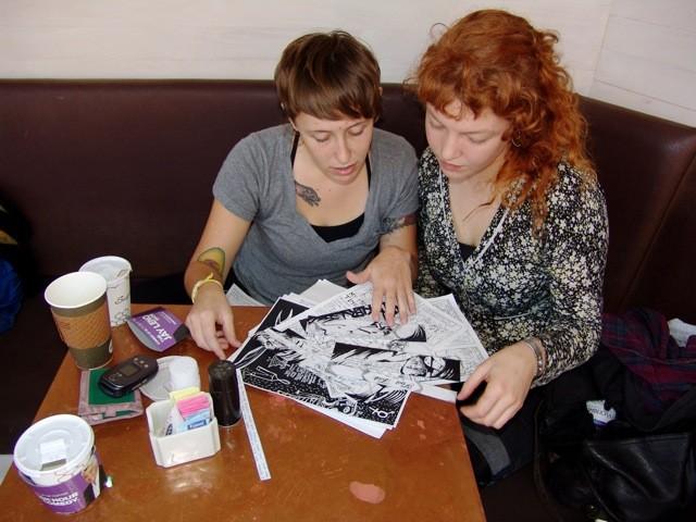 Liza Bley and Saiya Miller sort through loose zine pages at a cafe.