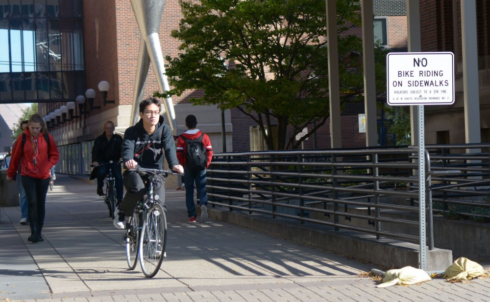 Students walk and bike through Scholars Walk on Friday. With an influx of bikers in the past year, UMPD ticketing for bicyclists has increased.