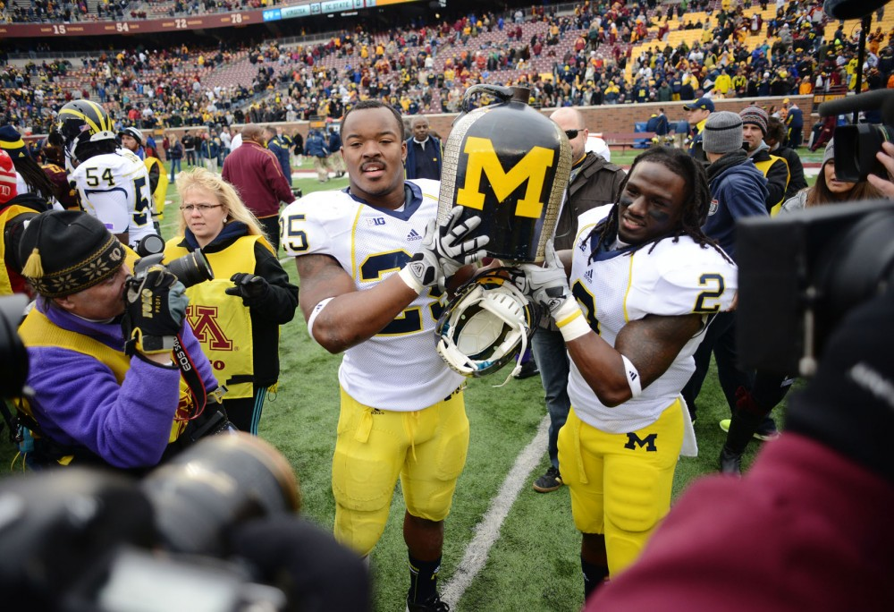 Michigan linebacker Kenny Demens and running back Vincent Smith carry Little Brown Jug after the Wolverines defeated Minnesota 35-13 on Saturday, Nov. 3, 2012, at TCF Bank Stadium.