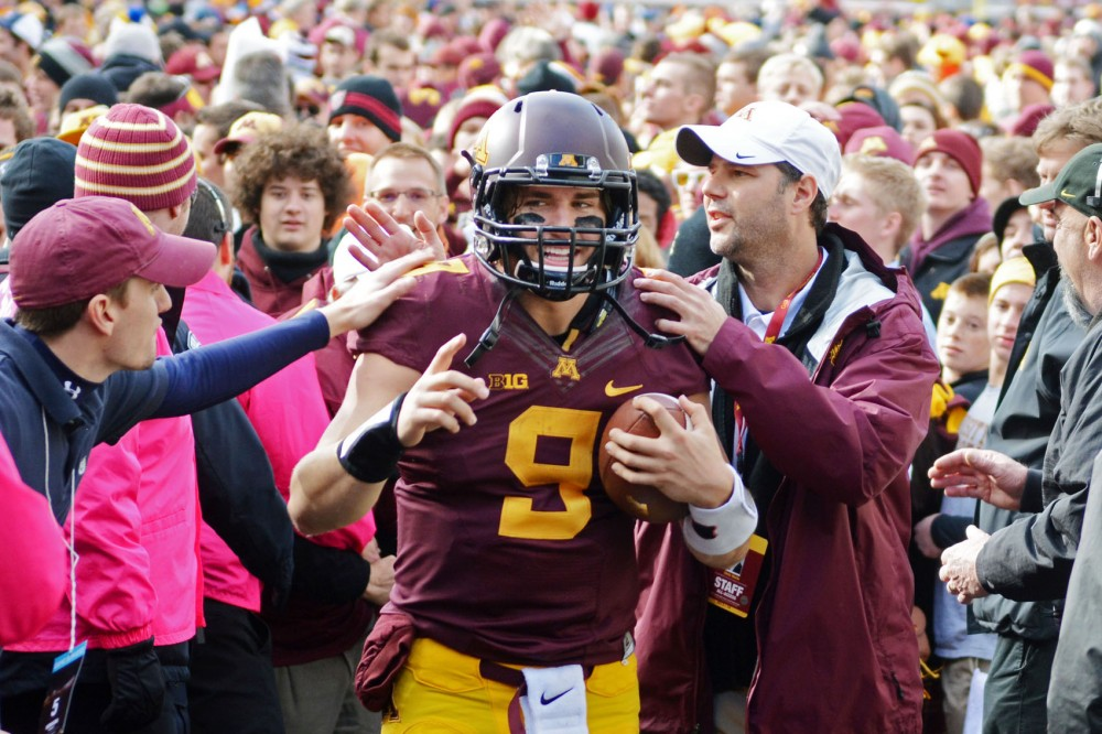 Minnesota fans congratulate quarterback Philip Nelson as he leaves the field after the team's victory over Nebraska on Saturday at TCF Bank Stadium.